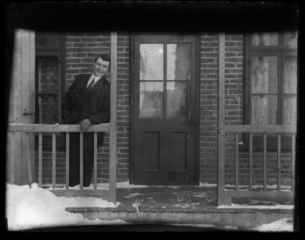 Man standing on porch in the snow.